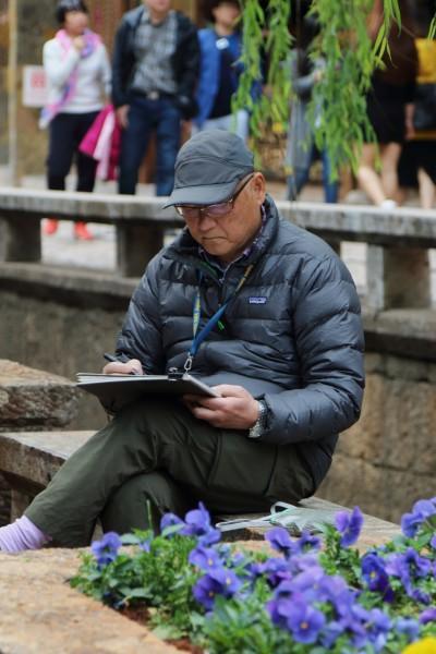 ,古城内很多提笔画字的人坐在凳子上,静静的描绘着他们眼中的